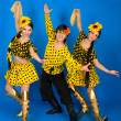 Two girls and a guy in the Russian national costumes dancing in — Stock Photo #8344808