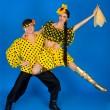 Young couple in Russian national costumes dancing in the studio — ストック写真