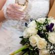 Bride with champagne and flowers — Stock Photo