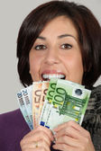 Woman with purple jacket and gray scarf with with euro bills — Stock Photo