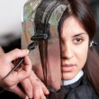 Stock Photo: Close up of hairdresser coloring woman's hair. Selective focus