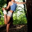 Stock Photo: Beautiful young woman stretching in a forrest after jogging