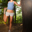 Beautiful young woman stretching in the woods after jogging — Stock Photo