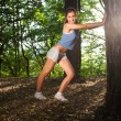 Stock Photo: Beautiful young woman stretching in a forrest after training