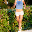 Beautiful fit young woman jogging in a park — Stock Photo