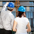 Construction engineer pointing on an area of the building on con — Stock Photo #10447572