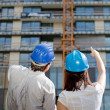 Stock Photo: Female construction engineer pointing on building at construct