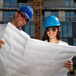 Stock Photo: Construction specialists reviewing bluprints at construction s