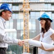 Happy construction specialists sealing the deal at a construction site — Zdjęcie stockowe