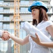 Young female construction engineer shaking hands at construction — Stock Photo