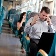 Businessman receiving bad news on a train — Stock Photo