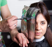 Hairdresser coloring woman's hair. Selective focus — Stock Photo