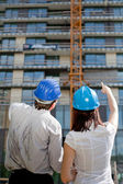 Female construction engineer pointing on a building at construct — Stock Photo