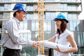 Happy construction specialists sealing the deal at a construction site — Stock Photo