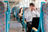 Stressed and tired businessman on a train — Stock Photo