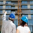 Construction engineer pointing on an area of the building on con — Stock Photo #10543602