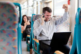 Happy businessman receiving good news on a train. selective focu — Stock Photo