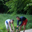 Fit happy couple stretching / warming up in a park — Stock Photo
