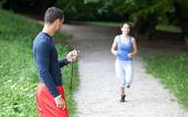 Persoonlijke trainer timing een vrouwelijke loper. selectieve aandacht. — Stockfoto