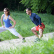 Cheerful fit young couple stretching / warming up in a park. Sel — Stock Photo #10611535