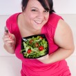 Happy overweight woman eating a salad. Selective focus. — Stock Photo