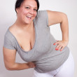 Cheerful overweight woman posing in sporty clothing - Stock Photo
