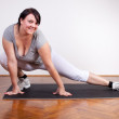 Happy overweight woman exercising/stretching — Stock Photo