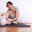 Size plus woman stretching on the floor — Stock Photo #8419332