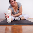 Size plus woman stretching on the floor — Stock Photo