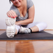 Cheerful overweight woman exercising/stretching — Stock Photo