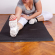 Stock Photo: Overweight woman stretching on the floor