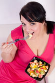 Overweight woman eating a fruit salad. — Stock Photo