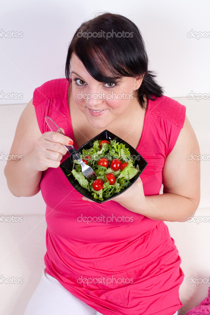 Overweight woman eating a salad. Selective focus. — Stock Photo #8419160