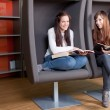 Stock Photo: Young women reading books in library. Selective focus.