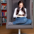 Happy young woman sitting and reading in a lounge chair in the l — Stock Photo