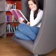 Young woman enjoying a good book in the library — Stock Photo