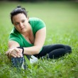 Plus sized woman stretching in a park. Shallow DOF. — Stock Photo