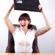 Angry businesswoman about to throw her laptop — Stock Photo