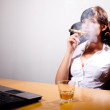 Young businesswoman chilling in her office, smoking a cigar and - Stock Photo