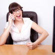 Angry young businesswoman receiving bad news over the phone. Off — Stock Photo #8848767