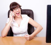 Angry young businesswoman receiving bad news over the phone. Off — Stock Photo