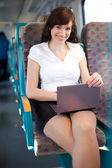 Beautiful young businesswoman using a netbook on the train / bus — Stock Photo