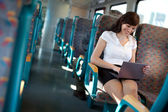 Happy young woman using a netbook on the train / bus — Stock Photo