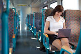 Young businesswoman on the move. Using laptop on the train / bus — Stock Photo