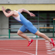 Professional sprinter's explosive start on the running track - Stock Photo