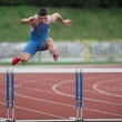 Professional sprinter jumping over a hurdle — Stock Photo #9790204