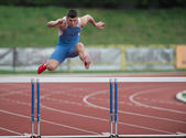 Professional sprinter jumping over a hurdle — Stock Photo