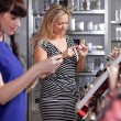 Girlfriends buying and testing cosmetics in a beauty store — Stock Photo