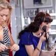 Women testing and buying face powder in a beauty shop — Stock Photo