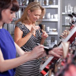 Young women testing and buying powder in a beauty store — Stock Photo